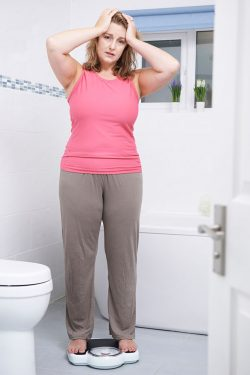 Unhappy Overweight Woman Weighing Herself On Scales In Bathroom