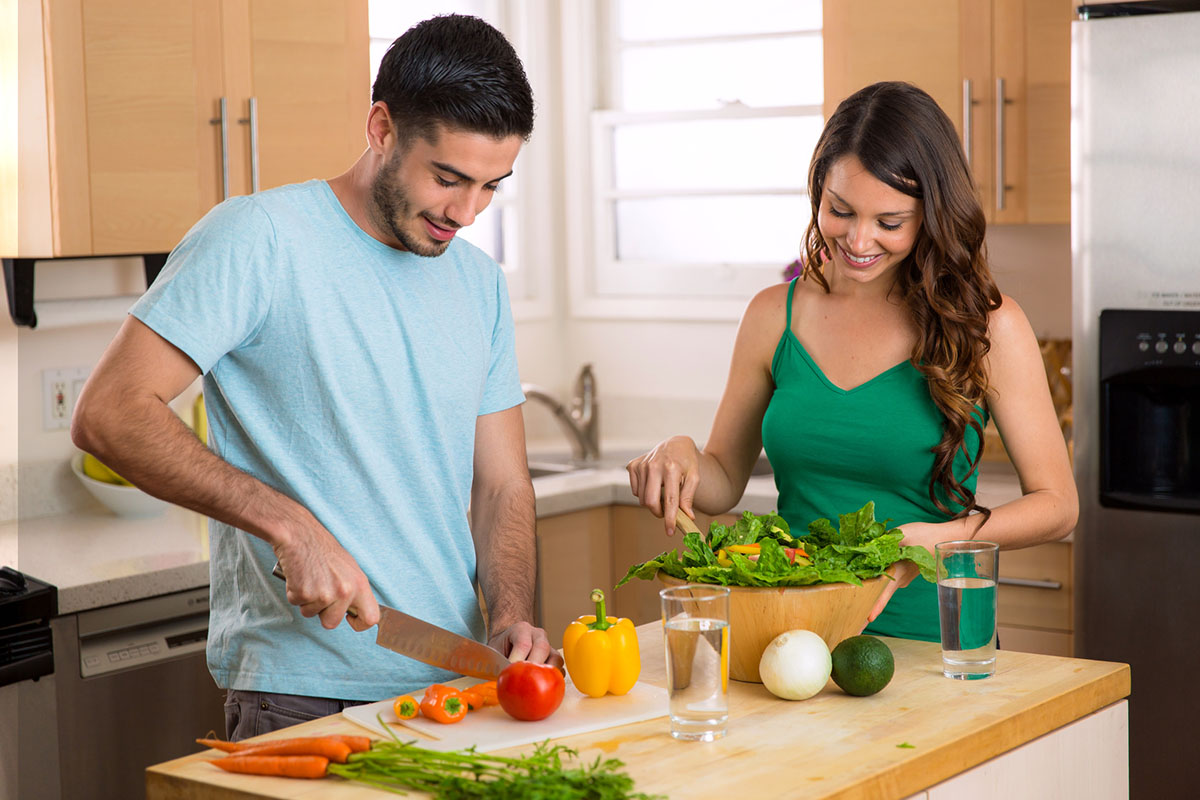 Attractive man and woman prepping low calorie dinner in kitchen