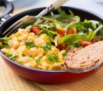 Scrambled eggs with fresh tomato and arugula salad in frying pan