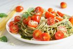 Pasta spaghetti with pesto sauce, fresh basil and cherry-tomatoes