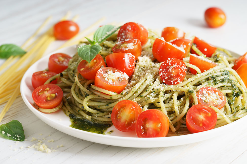 Pasta spaghetti with pesto sauce, fresh basil and cherry-tomatoes