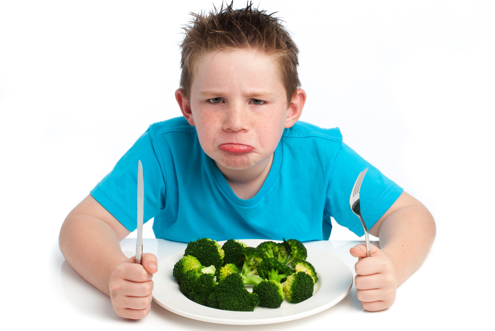 A young boy who is not happy about eating his broccoli.