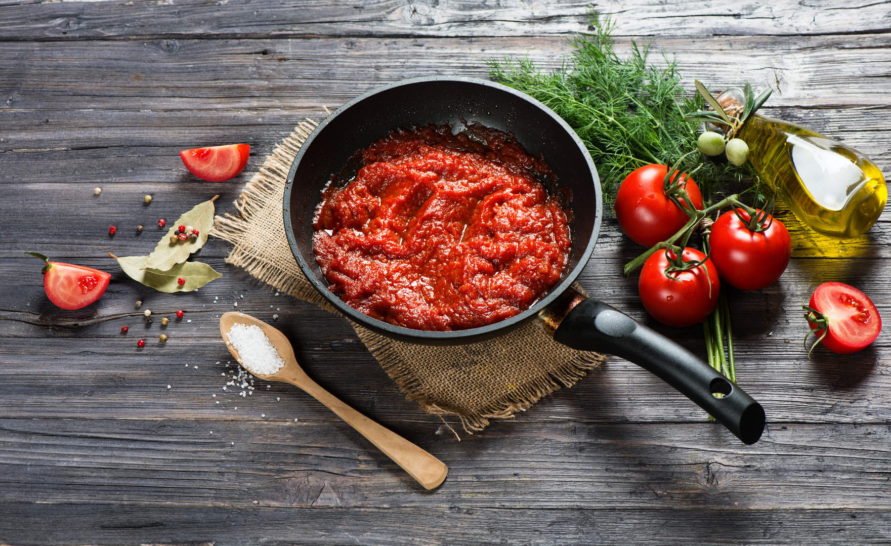 Tomato sauce in a pan and ingredients