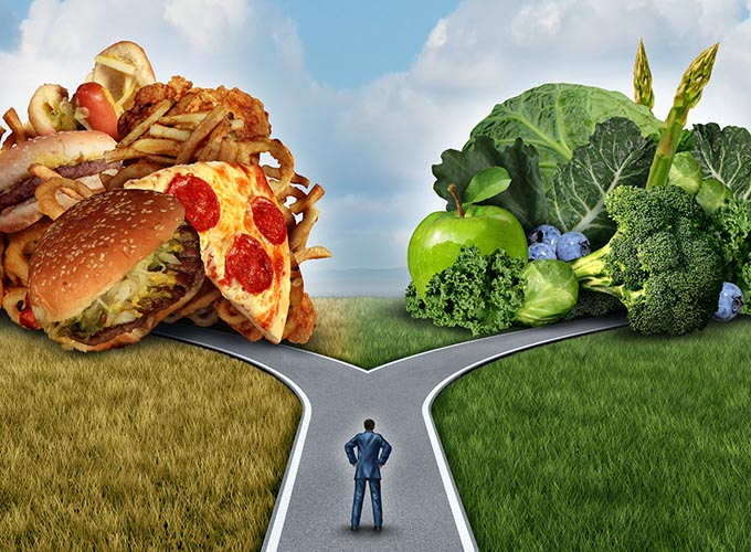 Diet decision concept and nutrition choices dilemma between healthy good fresh fruit and vegetables or greasy cholesterol rich fast food. Man on a crossroad trying to decide what to eat for the best lifestyle choice.